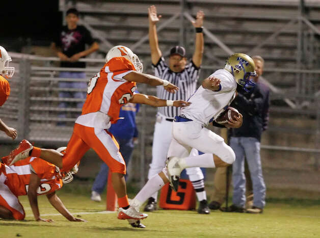 Kerrville-Tivy's Johnny Manziel (right) breaks away from Burbank's Ruben Cruz (left) to score a touchdown during their game at SAISD Sports Complex on November 14, 2008. Photo: Kin Man Hui, San Antonio Express-News / San Antonio Express-News