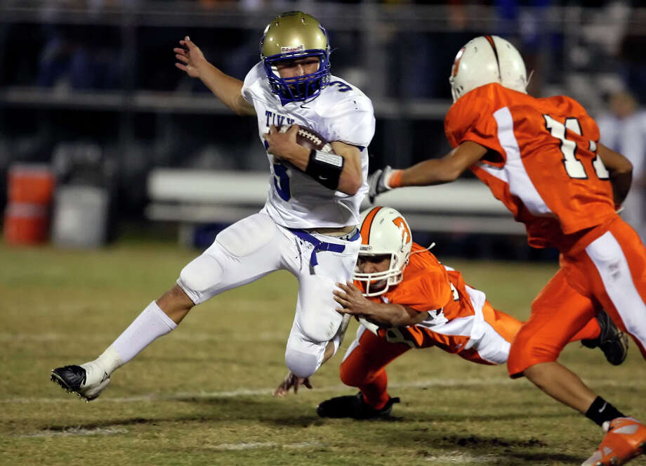 Kerrville-Tivy's Johnny Manziel (03) fights off Burbank defenders during their game at SAISD Sports Complex on November 14, 2008. Photo: Kin Man Hui, San Antonio Express-News / San Antonio Express-News