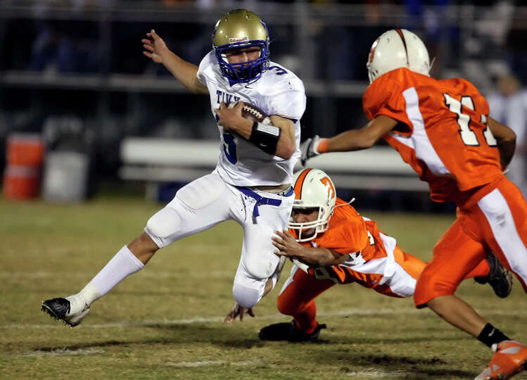Kerrville-Tivy's Johnny Manziel (03) fights off Burbank defenders during their game at SAISD Spor