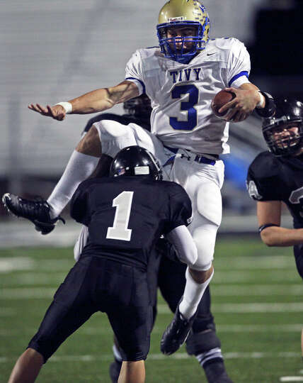 Antler quarterback Johnny Manziel jumps over a tackler on the sideline as he leads Kerrville Tivy