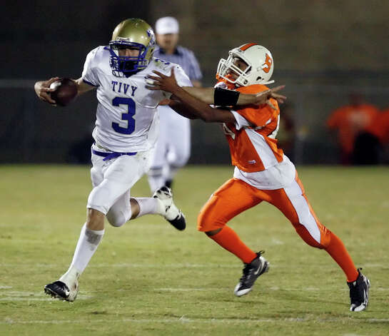 Kerrville-Tivy's Johnny Manziel (03) fights off a tackle from Burbank's Mario Trejo (right) during their game at SAISD Sports Complex on November 14, 2008. Photo: Kin Man Hui, San Antonio Express-News / San Antonio Express-News