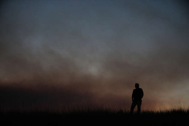 Erin McGee of Ellensburg watches the Taylor Bridge Fire burn near Cle Elum on Wednesday, August 15, 2012. The Taylor Bridge Fire has forced hundreds to evacuate and has burned dozens of homes. Photo: JOSHUA TRUJILLO / SEATTLEPI.COM