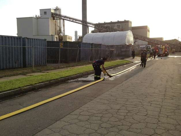 Firefighteres stretch hoses at a fire at O&G Industries asphalt plant on Bostwick Street on Thursday, Aug. 16, 2012 Photo: Frank Juliano