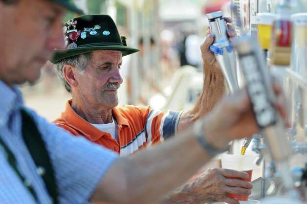 Frank Mohos of Stephentown, center, fills a Beck's Oktoberfest for a customer at the German-American Club of Albany booth during the Empire State Plaza Food Festival on Wednesday Aug. 15, 2012 in Albany, NY.  Fellow club member Tom Ohlmann of East Greenbush helps out at left.  (Philip Kamrass / Times Union) Photo: Philip Kamrass / 00018757A