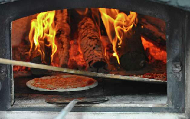 A pizza cooks in a 900 degree Fahrenheit wood fired pizza oven by Orapello's Wood Fired PIzza of Amsterdam, during the Empire State Plaza Food Festival on Wednesday Aug. 15, 2012 in Albany, NY.  Each pizza takes about 90 seconds to cook.  (Philip Kamrass / Times Union) Photo: Philip Kamrass / 00018757A