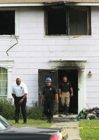 San Antonio Fire Department Chief Charles Hood (left) exits a building on the 300 block of West Norwood in North Central San Antonio where three people died and one person is in critical condition after a fire broke out Wednesday night. The three people that died were men with mental disabilities and a total of 13 people were living at the property when the fire took place. John Davenport/© 2012 San Antonio Express-News Photo: John Davenport, San Antonio Express-News / John Davenport/©San Antonio Exp