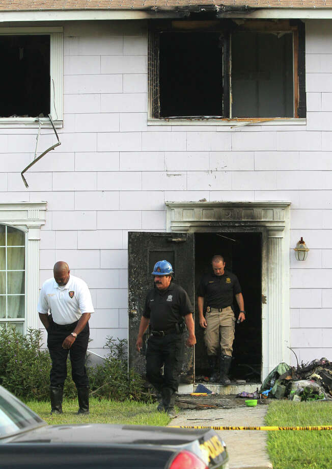 San Antonio Fire Department Chief Charles Hood (left) exits a building on the 300 block of West Norwood in North Central San Antonio where a fatal fire broke out Wednesday night. Photo: John Davenport, San Antonio Express-News / John Davenport/©San Antonio Exp