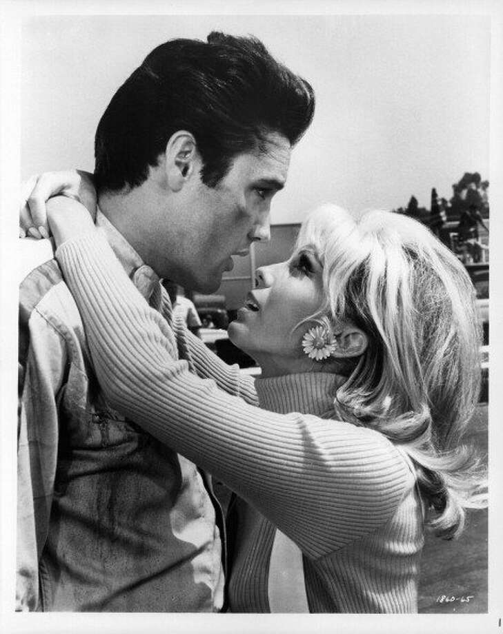 Nancy Sinatra has her arms around Elvis Presley in a scene from the film 'Speedway', 1968. (Photo by Metro-Goldwyn-Mayer/Getty Images) (Getty Images)