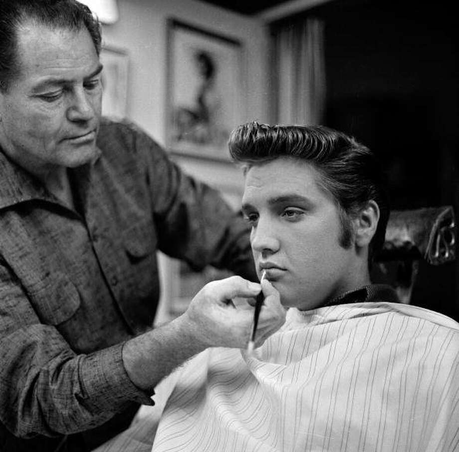 American singer and musician Elvis Presley sits in a chair as a make-up artist highlights his lips backstage at 'The Ed Sullivan Show,' Los Angeles, California, September 9, 1956. (Photo by CBS Photo Archive/Getty Images) (Getty Images)