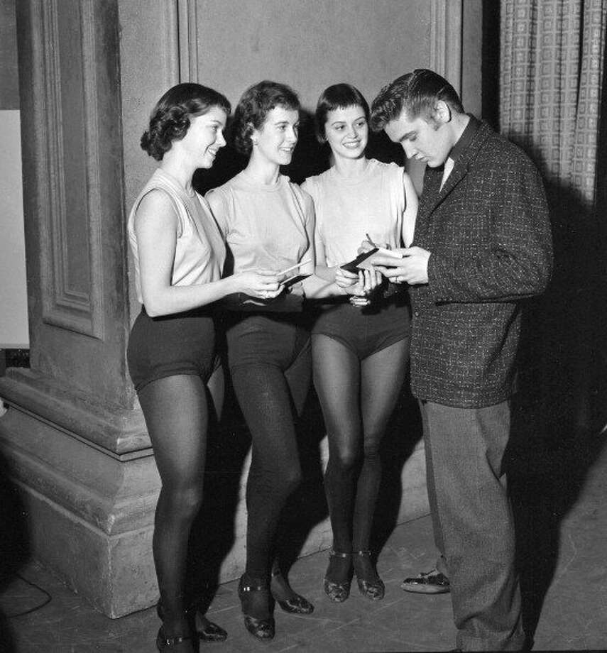 Elvis Presley (right) backstage on January 28, 1956, signing autographs for unidentified dancers. (Photo by CBS via Getty Images) (CBS via Getty Images)