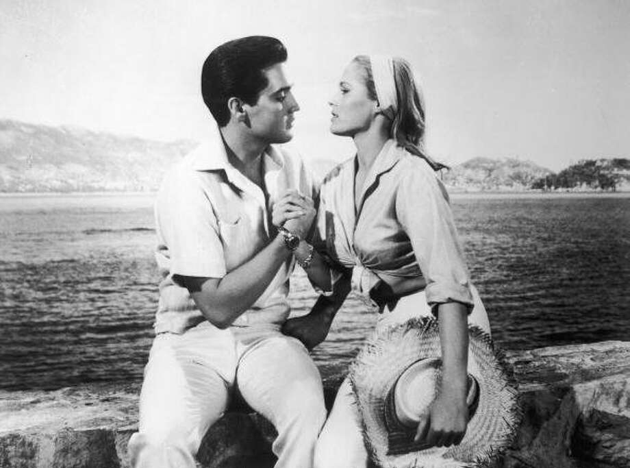 American singer and actor Elvis Presley (1935  -1977) holds the hand of Swiss born actor Ursula Andress in a still from the film, 'Fun in Acapulco,' directed by Richard Thorpe, 1963. (Photo by Paramount Studios/Courtesy of Getty Images) (Getty Images)