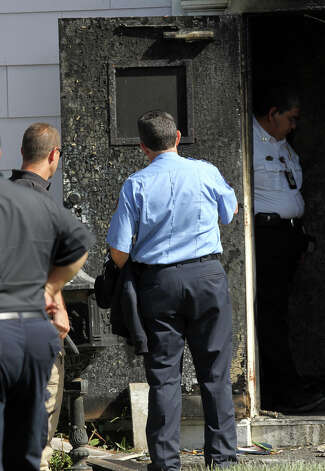 Investigators examine the charred front door of a residence on the 300 block of West Norwood Court that burned Wednesday night. Three men died in the blaze and another man is in critical condition. (Thursday August 16, 2012) John Davenport/© 2012 San Antonio Express-News Photo: John Davenport, San Antonio Express-News / John Davenport/©San Antonio Exp