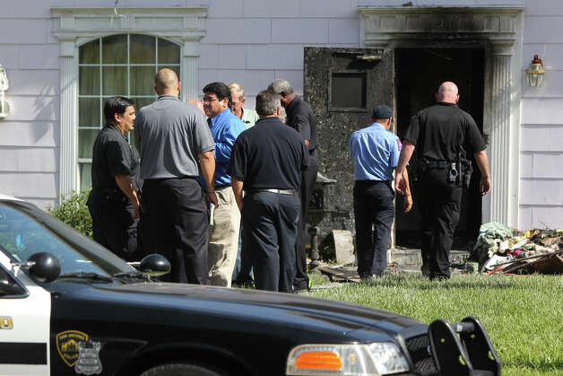 Fire and law enforcement personnel gather Wednesday August 16, 2012 in the front yard of a residence on the 300 block of West Norwood Court that burned Wednesday night killing three men. A fourth man is in critical condition. John Davenport/© 2012 San Antonio Express-News Photo: John Davenport, San Antonio Express-News / San Antonio Express-News