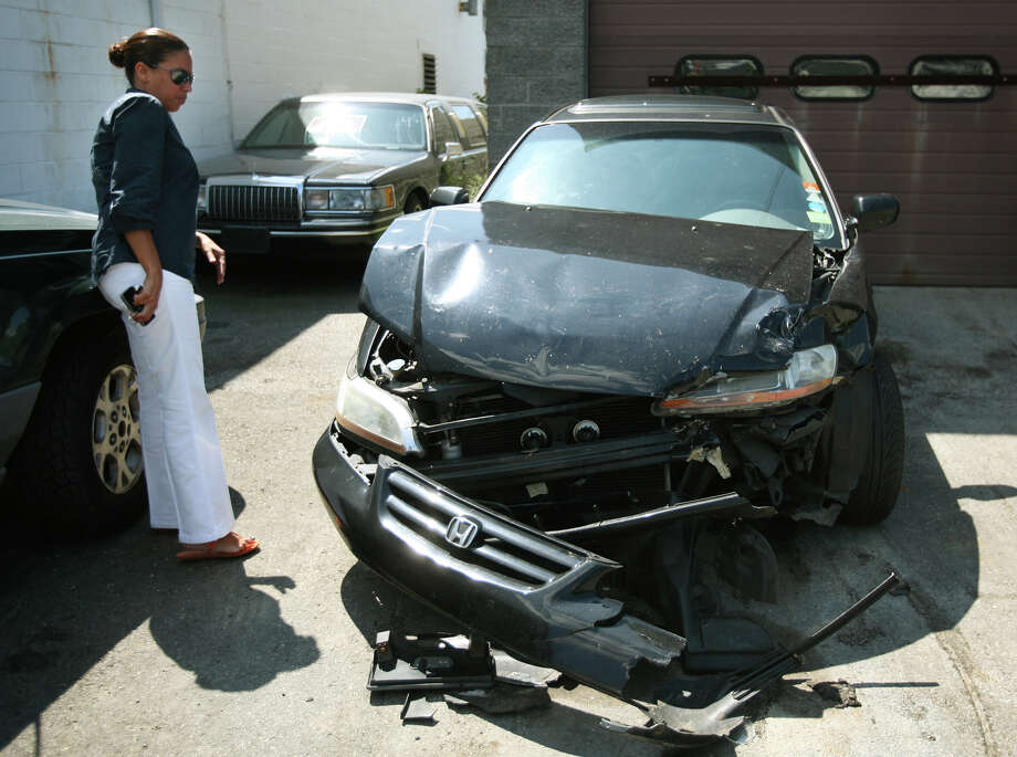 Mireya Porto of Bridgeport looks at her car, a 2002 Honda Accord, that was totalled in an accident with Bridgeport state representative candidate Christina Ayala on North Avenue in Bridgeport on Wednesday. Porto's daughter, Krystal Velez, was driving the car. Photo: Brian A. Pounds / Connecticut Post