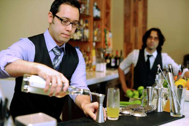 Steven Raul Martin mixes a cocktail at a new restaurant called Nao on Wednesday, Aug. 15, 2012. Adrian Sarabia watches. Photo: Billy Calzada, San Antonio Express-News / © San Antonio Express-News