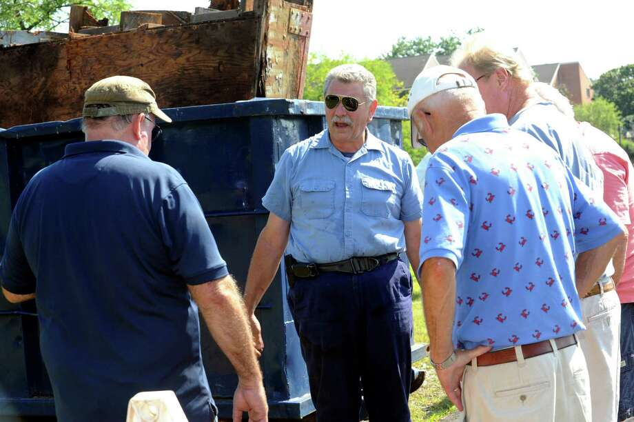 Deputy Fire Marshal Shawn McDonnell, center, speaks about his boat, the Mudhen, and its history Thursday, Aug. 16, 2012, as it was being dismantled at Cos Cob Harbor. Photo: Helen Neafsey / Greenwich Time