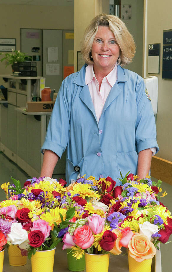LaVonne Kramer delivers flowers to patients at Norwalk Hospital through a volunteer program she planted the seed for. Photo: Jeff Scholl / Contributed Photo