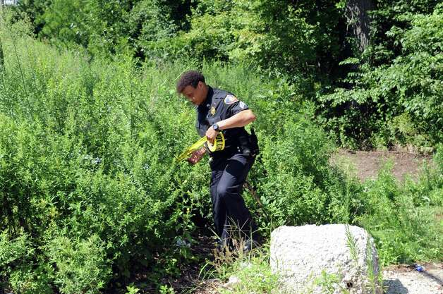 Police work at the entrance to a walking trail on Long Ridge Road which leads to a clearing where a dirt-bike accident caused the death of a 14-year-old and life-threatening injuries to his 16-year-old brother on Thursday, August 16, 2012. Photo: Lindsay Niegelberg / Stamford Advocate