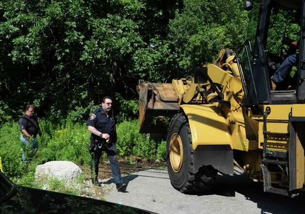 A pay-loader is used to widen the trail so police vehicles could access the walking trail on Long Ridge Road which leads to a clearing where a dirt-bike accident caused the death of a 14-year-old and life-threatening injuries to his 16-year-old brother on Thursday, August 16, 2012. Photo: Lindsay Niegelberg / Stamford Advocate