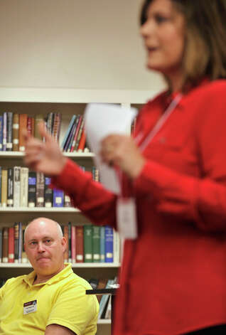 "Toastmaster Dave Wheeler, left, watches Caryn Swensen give her ""Motivation Palooza 2012 Evaluation"" speech during a WestConn Toastmasters Club meeting at the Wooster School library in Danbury on Thursday, Aug. 16, 2012. Photo: Jason Rearick / The News-Times"