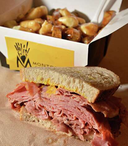 Classic Poutines and a Montreal Smoked Meat Sandwich from Shirley's Montreal Poutine, under the carousel at Saratoga Race Course Wednesday Aug. 15, 2012. (John Carl D'Annibale / Times Union) Photo: John Carl D'Annibale / 00018831A