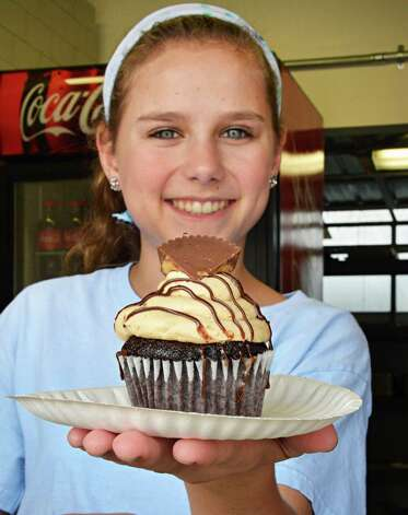Rachel Shaver, 15, of Wilton offers up a peanutbutter cup cupcake at Bettie's Cakes on  Restaurant Row at Saratoga Race Course Wednesday Aug. 15, 2012. (John Carl D'Annibale / Times Union) Photo: John Carl D'Annibale / 00018831A