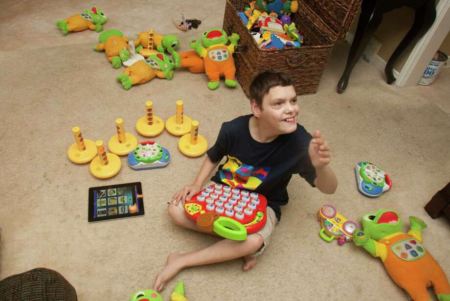 Nolan Farris, 11, plays with his toys at his home in Missouri City. Nolan is autistic and does not speak.  His parents, Jody and Ryan Farris, have created an extensive, hundred-dollar iPhone/iPad app that helps their son communicate with others. Photo: J. Patric Schneider / © 2012 Houston Chronicle