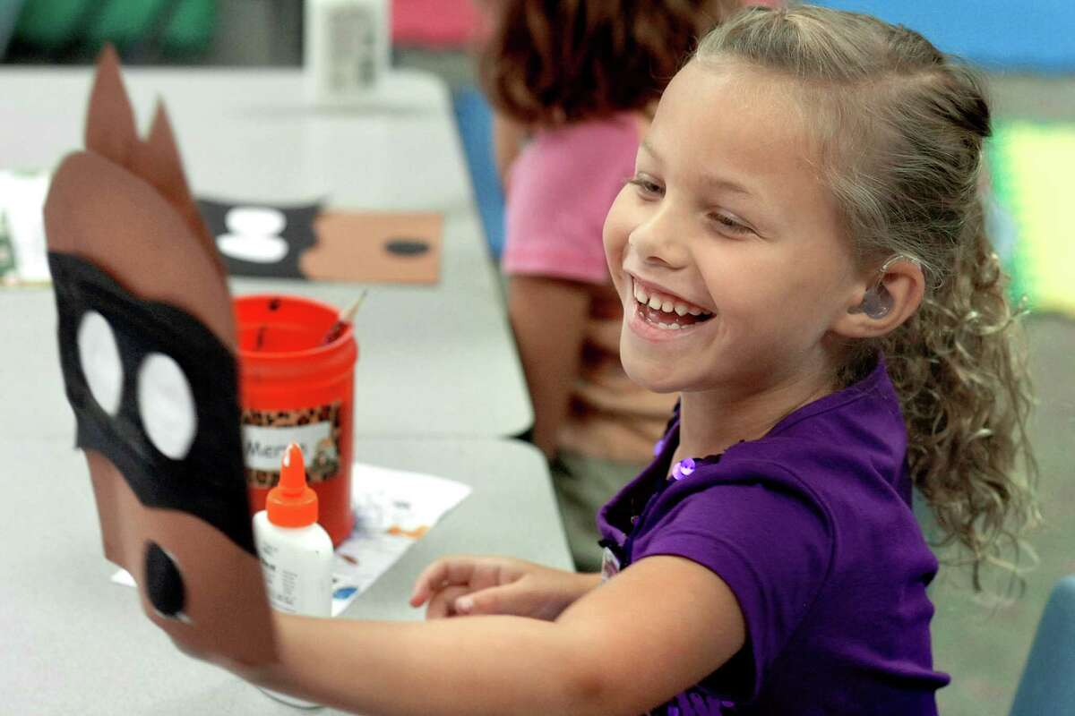 Meryn Norman shows her paper puppet to classmates Tuesday, Aug. 14, 2012, in Patty Steele's kindergarten classroom at Southwood Elementary School in Wabash County, Ind. Tuesday was the first day of classes at the school. (AP Photo/Wabash Plain Dealer, Jeff Morehead)