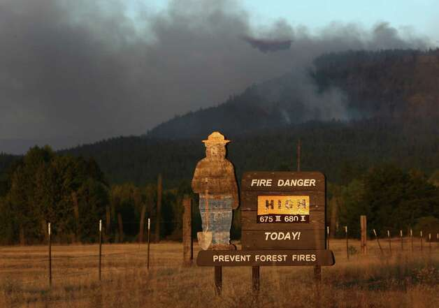 A sign outside Cle Elum advises the fire danger as the Taylor Bridge Fire burns on a hillside outside of town on Wednesday, August 15, 2012. The Taylor Bridge Fire has forced hundreds to evacuate and has burned dozens of homes. Photo: JOSHUA TRUJILLO / SEATTLEPI.COM