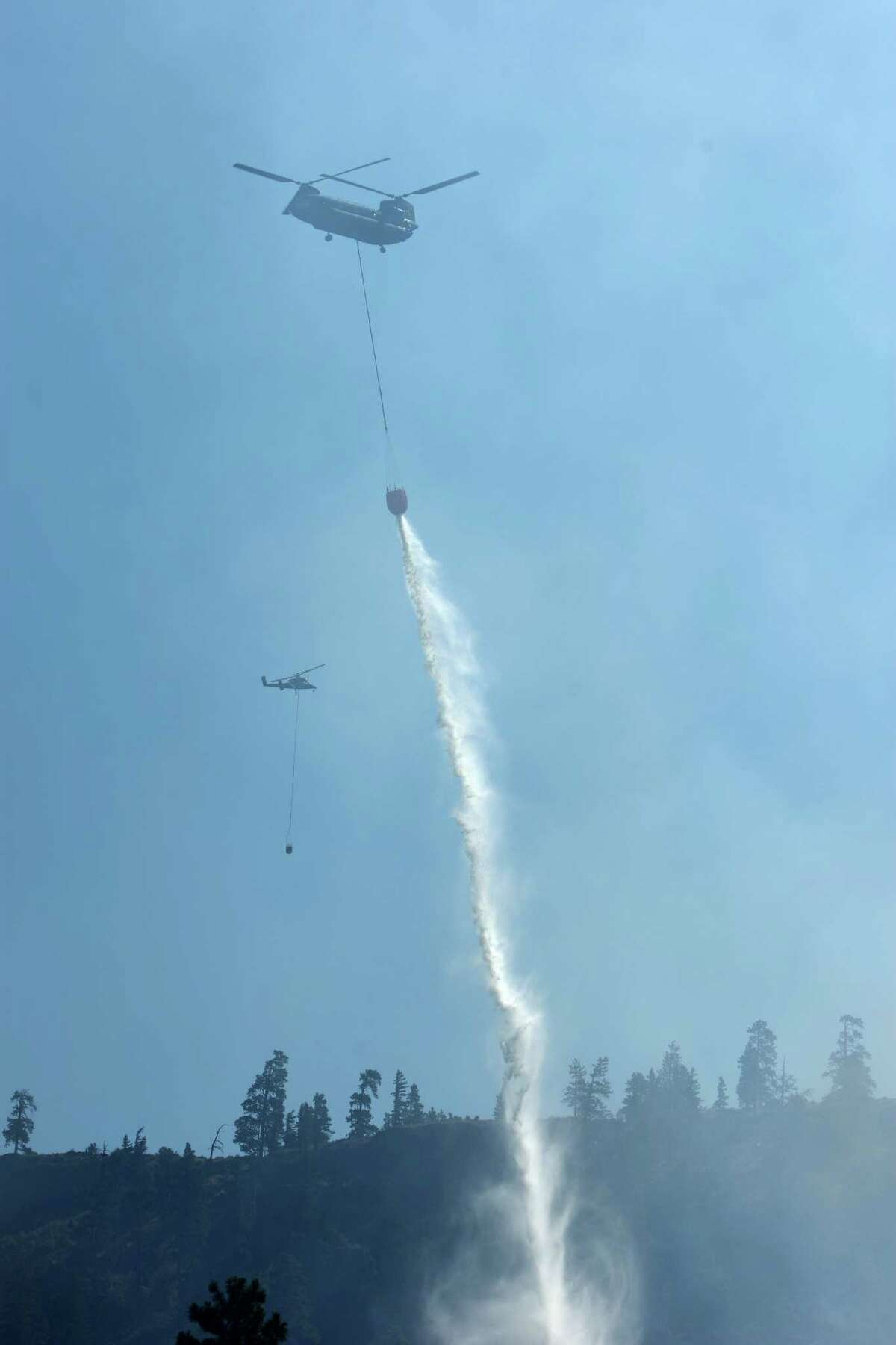 Helicopters drop water above Hidden Valley Ranch where fire crews worked to halt progression of the Taylor Bridge Fire on Thursday, August 16, 2012. The Taylor Bridge Fire has forced hundreds to evacuate and has burned dozens of homes.