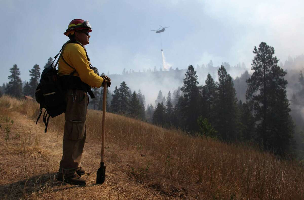 Tracy Summers of Toledo, Wash. monitors the scene above Hidden Valley Ranch where fire crews worked to halt progression of the Taylor Bridge Fire on Thursday, August 16, 2012. The Taylor Bridge Fire has forced hundreds to evacuate and has burned dozens of homes.