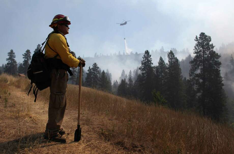 Tracy Summers of Toledo, Wash. monitors the scene above Hidden Valley Ranch where fire crews worked to halt progression of the Taylor Bridge Fire on Thursday, August 16, 2012. The Taylor Bridge Fire has forced hundreds to evacuate and has burned dozens of homes. Photo: JOSHUA TRUJILLO / SEATTLEPI.COM