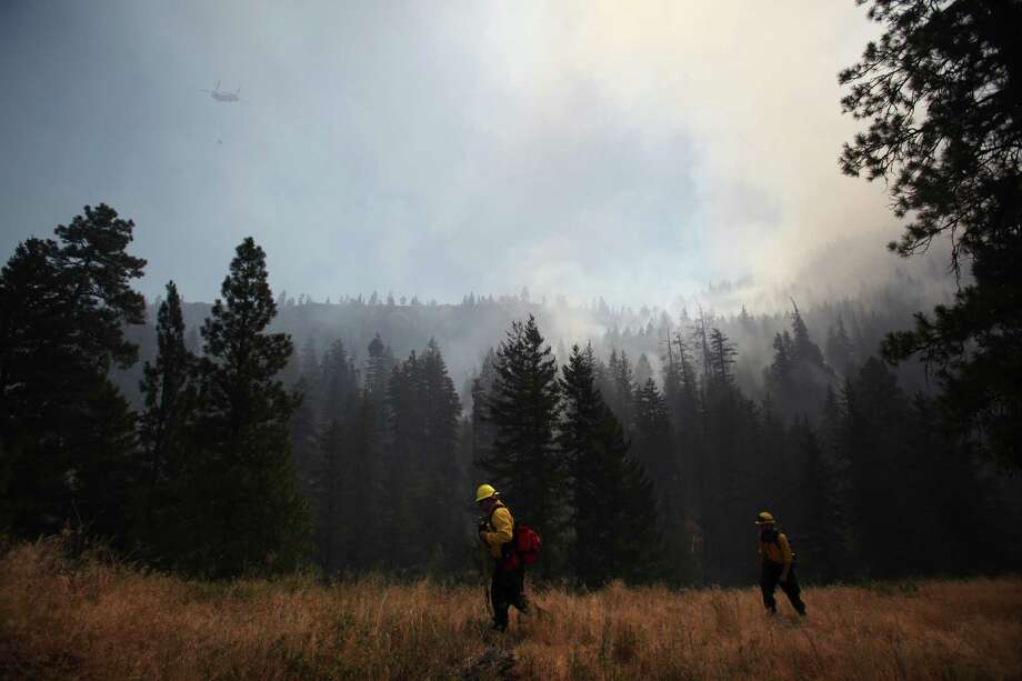 Firefighters monitor the scene above Hidden Valley Ranch where fire crews worked to halt progression of the Taylor Bridge Fire on Thursday, August 16, 2012. The Taylor Bridge Fire has forced hundreds to evacuate and has burned dozens of homes. Photo: JOSHUA TRUJILLO / SEATTLEPI.COM