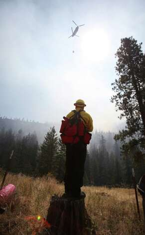 A firefighter monitors the scene above Hidden Valley Ranch where fire crews worked to halt progression of the Taylor Bridge Fire on Thursday, August 16, 2012. The Taylor Bridge Fire has forced hundreds to evacuate and has burned dozens of homes. Photo: JOSHUA TRUJILLO / SEATTLEPI.COM