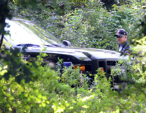 Sgt. Andrew Gallagher of the Stamford Police Crash Analysis team conducts an investigation at the Levine Site, an undeveloped park off of Long Ridge Road where a fatal dirtbike accident took place in Stamford, Conn., August 16, 2012. Kevin Bella, 14, was killed and his 16-year-old brother, Brandon, suffered life-threatening injuries in a dirtbike accident Thursday afternoon in an undeveloped city park off Long Ridge Road. The site was once used as a city dump site for leaves. It sits along the banks of the Rippowam River and is a popular spot for dirtbikes. Photo: Keelin Daly / Stamford Advocate