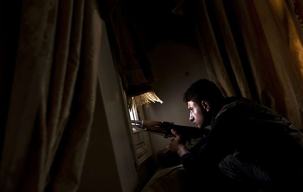 A member of the Free Syrian Army (FSA) tries to spot positions held by government forces from a residential building on the outskirts of the Salaheddin neighbourhood of the northern Syrian city of Aleppo on August 14, 2012. With the West still refusing to arm Syria's opposition in the bloody fight against the regime, rebels in the flashpoint city of Aleppo warn that they could turn to Al-Qaeda for help. AFP PHOTO / ACHILLEAS ZAVALLISACHILLEAS ZAVALLIS/AFP/GettyImages