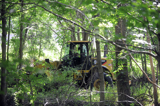 A pay-loader clears a path as Stamford Police investigate the scene of a fatal dirtbike accident at the Levine Site, an undeveloped park off of Long Ridge Road in Stamford, Conn., August 16, 2012. Kevin Bella, 14, was killed and his 16-year-old brother, Brandon, suffered life-threatening injuries in a dirtbike accident Thursday afternoon in an undeveloped city park off Long Ridge Road. The site was once used as a city dump site for leaves. It sits along the banks of the Rippowam River and is a popular spot for dirtbikes. Photo: Keelin Daly / Stamford Advocate