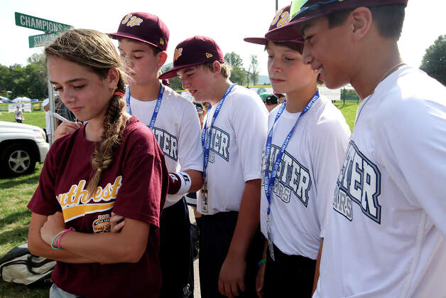 Sarina Lauchle, 12, (cq), left, of Belton, Pennsylvania, gets her tee-shirt autographed by members of the McAllister Park National Little League on the first day of the 2012 Little League World Series in South Williamsport, Pa., Thursday, Aug. 16, 2012. The team, representing the Southwest Champions will face off with the Mid-Atlantic Champions from Parsippany, New Jersey, Friday afternoon. From left, Landry Wideman, 13, Carter Elliott, 13, Mason Moore, 12 and Grant Gomez, 13 sign the shirt. Photo: Jerry Lara, San Antonio Express-News / © 2012 San Antonio Express-News