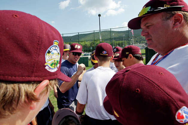The McAllister Park National Little League team Coach Kyle Elliott, center in blue, and Manager Jack Wideman, Jr, right, wrap up practice with the team on the first day of the 2012 Little League World Series in South Williamsport, Pa., Thursday, Aug. 16, 2012. The team, representing the Southwest Champions will face off with the Mid-Atlantic Champions from Parsippany, New Jersey, Friday afternoon. Photo: Jerry Lara, San Antonio Express-News / © 2012 San Antonio Express-News