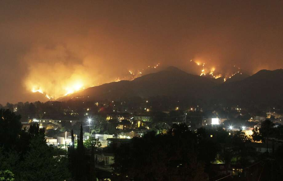 FILE - This Aug. 31, 2009 file photo shows the Station Fire burning on the hillsides of the Tujunga area of Los Angeles. The U.S. Forest Service has decided to allow nighttime aerial attacks on wildfires in Southern California in a change of policy spurred by controversy over the 2009 Station Fire blaze that grew to 250 square miles and threatened Los Angeles suburbs, congressional representatives announced Thursday Aug. 16, 2012. (AP Photo/John Lazar, file) Photo: John Lazar, Associated Press