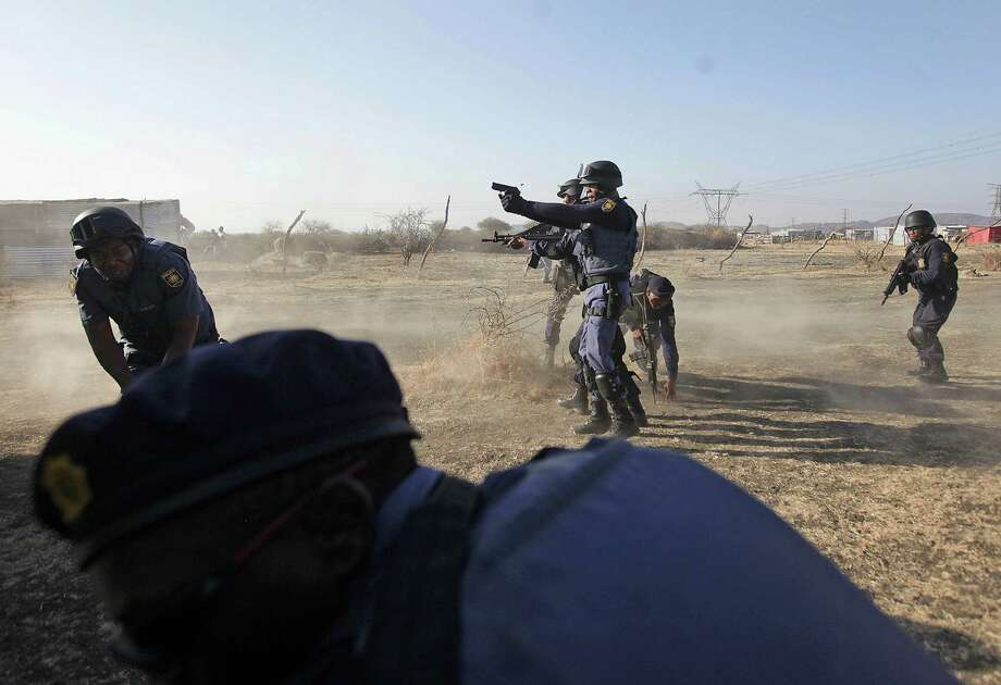 Police open fire on a crowd of striking miners at the Lonmin platinum mine near Rustenburg, South Africa. The area was strewn with dead and wounded. Photo: Associated Press / AP