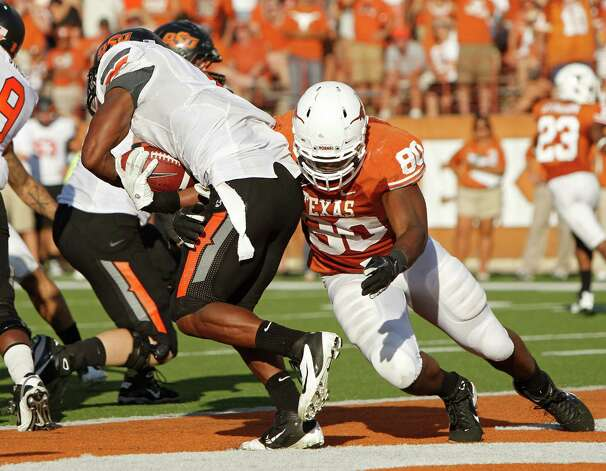 Defensive end Alex Okafor of Texas tackles running back Joseph Randle of Oklahoma State in the fourth quarter on October 15, 2011 at Darrell K. Royal-Texas Memorial Stadium in Austin. Photo: Erich Schlegel, Getty Images / 2011 Getty Images