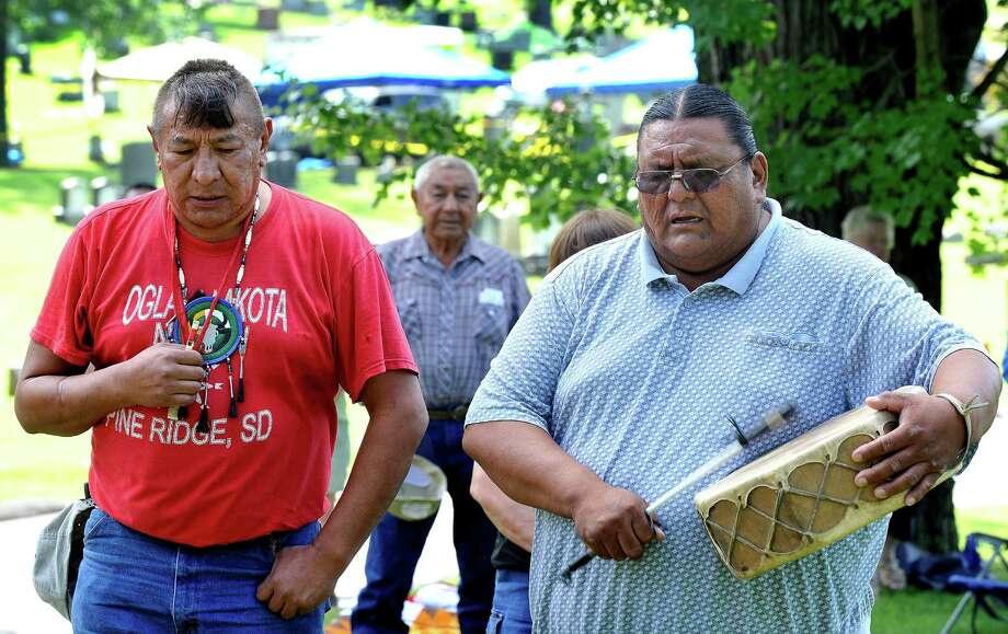 John Afraid Of Hawk, left, and Richard Red Elk, right, frame Daniel Afraid Of Hawk during a naming ceremony at Wooster Cemetery in Danbury Thursday, Aug. 16, 2012. Photo: Michael Duffy