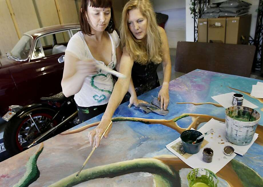Laurie Marshall (right) helped Lindsay Rucker with the color choices for moss on a tree for the mural project. Photo: Brant Ward, The Chronicle