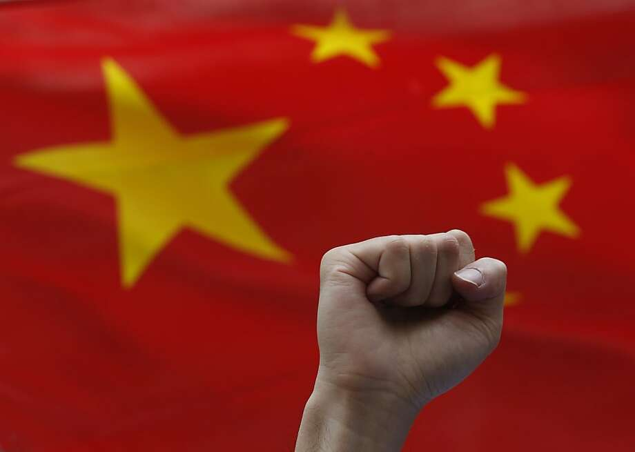 "An anti-Japan protester shows a clenched fist in front of a Chinese national flag during a rally outside the Japanese Consulate General in Hong Kong Thursday Aug. 16, 2012 as they demand Japanese government to release Chinese activists arrested in Japan after landing on Uotsuri Island, one of the islands of Senkaku in Japanese and Diaoyu in Chinese. China's official Xinhua News Agency said the arrests of the 14 people, who included Hong Kong residents and mainland Chinese, had caused tensions over its territorial dispute with Japan to surge ""to a new high."" Photo: Kin Cheung, Associated Press"