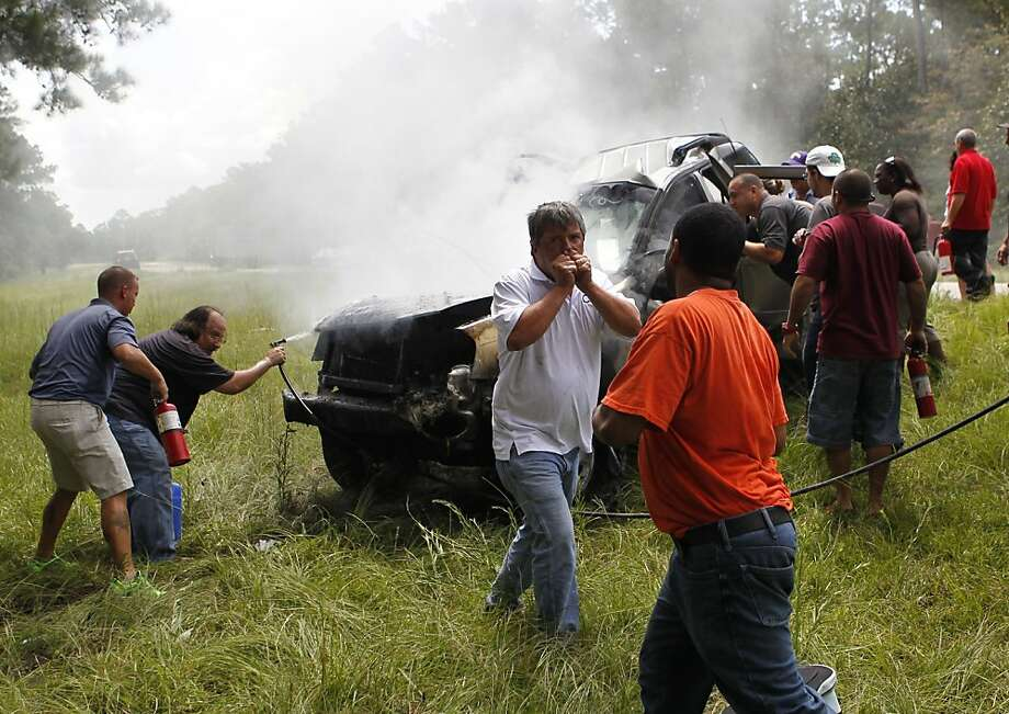 Passers-bye rescue a woman pinned in a burning car on Interstate 10 in Hancock County, Miss., Thursday, Aug. 16, 2012. The fire was extinguished by the hose of a cement mixer, and fire extinguishers from nearby 18 wheelers. The woman was then extracted from the wreckage by the civilians as rescue personnel arrived, and she and her handicapped child, who was removed from the wreckage early, were airlifted from the scene.  Photo: Gerald Herbert, Associated Press