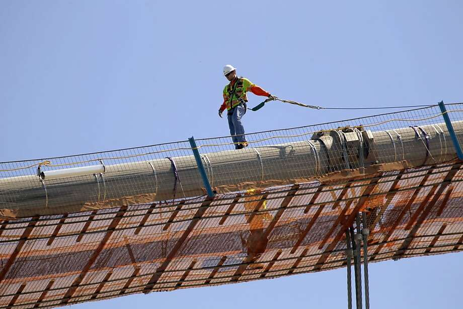 "A work crew tightens the pressure on suspension cables of the new eastern span of the Bay Bridge on Thursday, August 16, 2012, in San Francisco, Calif., Crews on the new east span of the Bay Bridge were preparing to start ""transfering the load"" or lifting the suspension section of the new bridge onto the suspension cables and off of the temporary trestles that have supported it during construction. Photo: Carlos Avila Gonzalez, The Chronicle"