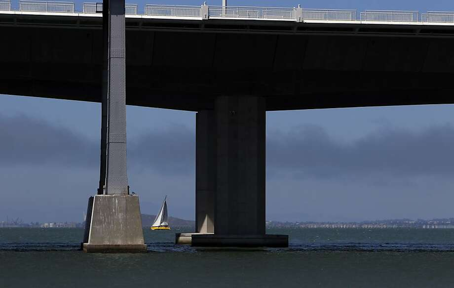 A sailboat on San Francisco Bay is framed between the old and new supports for the east span of the Bay Bridge. Photo: Carlos Avila Gonzalez, The Chronicle