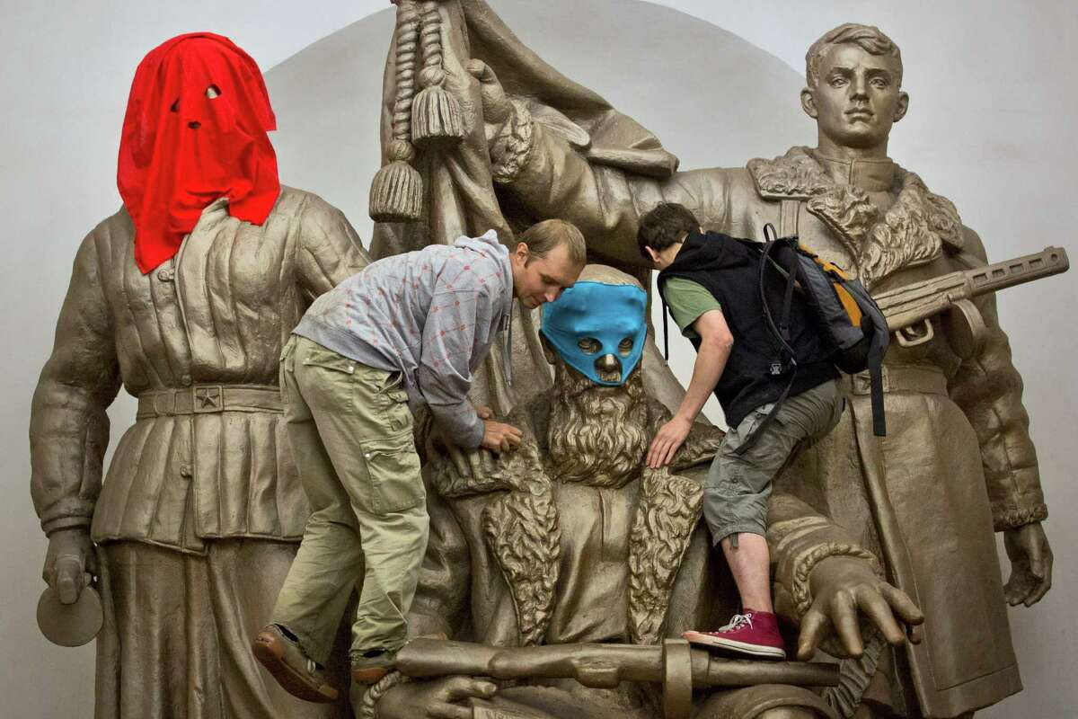 Pussy Riot punk group supporters place masks on a monument to WWII heroes to resemble Pussy Riot members, at an underground station in Moscow on Friday, Aug. 17, 2012. Three group members who were jailed in March following a guerrilla performance denouncing President Vladimir Putin in Moscow's main cathedral have unwillingly emerged as vivid ?- and very different ?- characters. They await a verdict Friday on charges of hooliganism motivated by religious hatred. (AP Photo/Yevgeny Feldman, Novaya Gazeta)