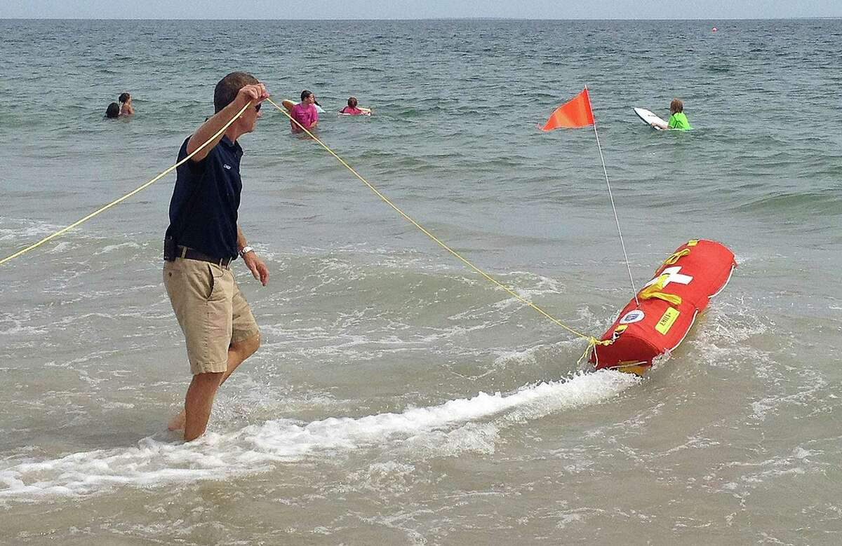 In this Wednesday, Aug, 8, 2012 photo, Misquamicut, R.I., Fire Chief Louis Misto, left, holds a line attached to the EMILY remote-control lifesaving device as it propels itself in the water and away from the shore at Old Town Beach, in Westerly, R.I. EMILY, an acronym for Emergency Integrated Lifesaving Lanyard, is a small watercraft fitted with a flotation device and can go up to 22 mph, allowing it to get to people more quickly, and in some cases more safely, than any human. (AP Photo/Michelle R. Smith)